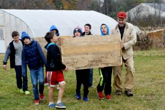 Kids moving a garden bed they built at Atkins Field