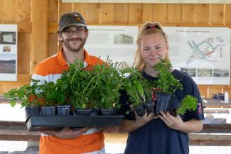 Harmoney and Josh Peets pose with plants during their Grow Your Own Workshop